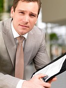 Close_up portrait of a successful handsome business man holding a folder