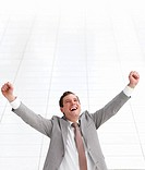 Close_up portrait of a young successful happy business man celebrating success in joy with arms wide open