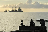 Dili (East Timor): kids at the city´s beach, near the harbor, at sunset
