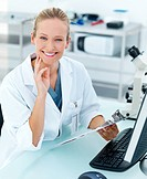 Happy female researcher by microscope smiling