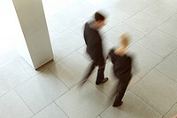 Businessman and businesswoman walking in lobby, Munich, Bavaria, Germany