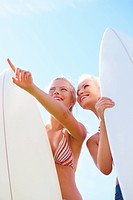 Pretty young teenage girls holding surfboards and pointing