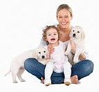 Woman holding a baby girl and two puppies Happiness, family and friendship