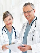 Closeup of a happy senior doctors standing together with reports