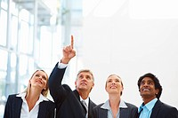 Mature business man pointing upwards showing something to his colleagues