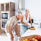 Mature woman preparing salad while her husband is having wine