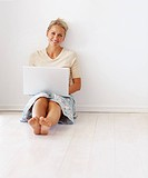 Happy mature woman working on a laptop while sitting on the floor