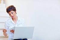 An attractive business woman sitting at home with laptop