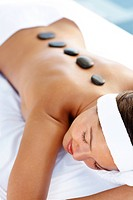 Sexy female during the hot stone therapy