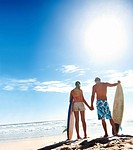 Rear view of a couple holding surf boards with the blue sky as the background
