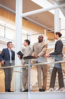 Portrait of a business group standing by a glass railing