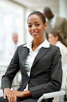 A successful satisfied African American business woman sitting on a chair in the office