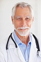 Closeup portrait of a senior old mature male doctor isolated over grey background