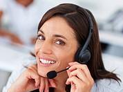 Closeup portrait of a happy beautiful operator wearing a working on a headphone
