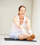 Portrait of smiling fit mature woman working out on a yoga mat