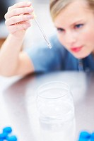 Closeup of young female doctor using a dropper