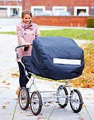 Young pretty woman walking baby around in pram