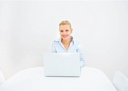 Smiling young woman using laptop in copy space