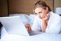 Portrait of a young woman lying on bed and using laptop