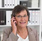 Closeup portrait of a mature business woman using cellphone, bookshelf in background