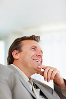 Happy middle aged business man looking away in a happy thought