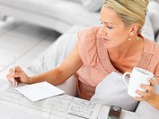 Mature woman at home seeking for jobs in the newspaper