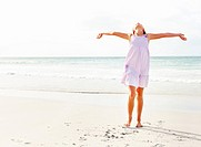 Young girls enjoying at the sea shore with her hands outstretched