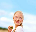 Cute young female eating a green apple with the blue sky as the background