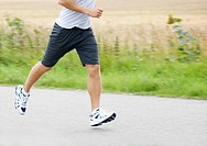 Young male athlete jogging at countryside