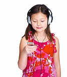 Little girl listening to music with headphones and MP3 player