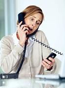 Portrait of surprised mature businesswoman multitasking by handling telephone calls
