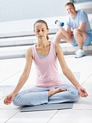 Portrait of a pretty middle aged woman meditating in the lotus position at the gym