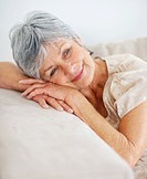 Closeup portrait of a smiling old woman relaxing on a couch