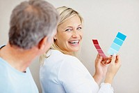 Happy middle aged couple thinking of which color to paint their wall