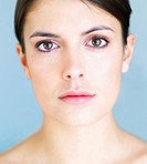 Closeup portrait of a beautiful young woman with a gentle makeup over blue background