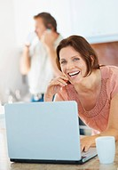 Portrait of a happy woman using laptop and man on phone in the background