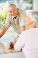 Happy beautiful elderly couple enjoying coffee at table