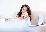 Portrait of a smiling middle aged woman with coffee cup and laptop on couch