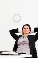 Relaxed successful middle aged business woman smiling at work