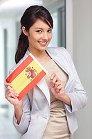 Portrait of a pretty young woman holding Spain´s flag