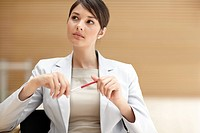 Portrait of a working woman thinking with a pen in hand