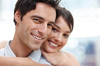 Closeup portrait of a cute young couple together with arms around