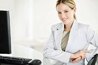Portrait of a smiling young business woman with computer in office