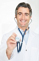 Portrait of a smiling mature male doctor holding a stethoscope for medical checkup