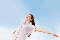 Portrait of a beautiful young female spreading her arms wide open against sky