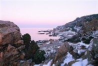 A rocky beach covered with snow, Sweden,