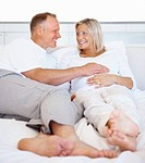 Happy mature couple lying in bed with man touching his pregnant wife belly