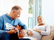 Mature man plays the guitar for his pregnant wife