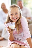 Closeup portrait of cute young girl holding a glass of milk while her parents sitting in background at home