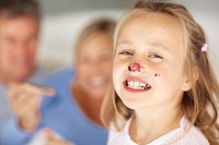 Closeup portrait of cute young girl having jam on her nose with parents having breakfast in the background